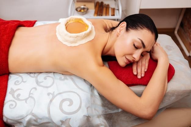 Spa-kast. aantrekkelijke vlekkeloze dame met donker haar dat haar lichaam aantast met ayurveda-procedure in professionele schoonheidssalon
