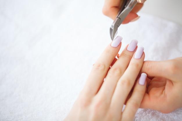 Spa manicure. french manicure bij kuuroordsalon. de vrouw dient een spijkersalon in die een manicureprocedure ontvangen. manicure procedure.