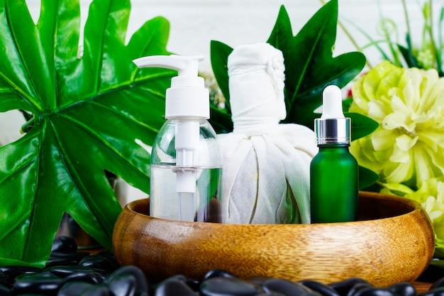 Spa-massage-instelling met druppelaar met serumoliefles en kruidenkompresballen op zwarte steen