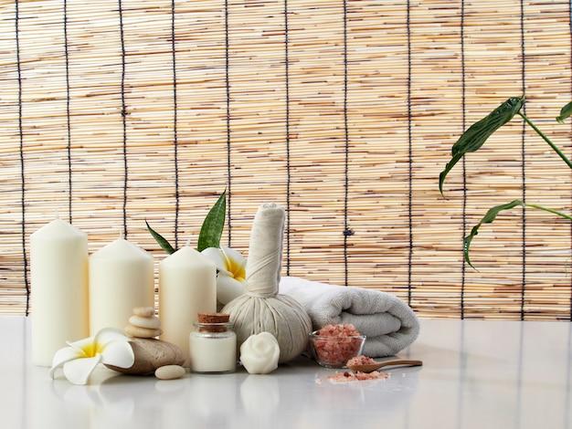 Spa massageconcept, kruidenkompres, crème, bloemenzeep, geurkaars op een witte tafel, bamboegordijn