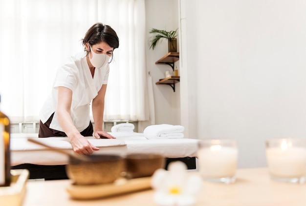Spa-massagetherapeut met gezichtsmasker die in het nieuwe normaal werkt
