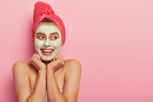 Spa meisje smeert modderige textuur over gezicht, heeft een blije blik, houdt handen onder de kin, kijkt weg met een glimlach, hydrateert en kalmeert de huid, draagt een rode handdoek op het hoofd, overtollige olieproductie, staat naakt binnen