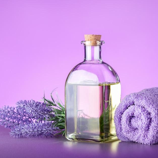 Spa met lavendel. fles etherische olie van lavendel met verse lavendelbloemen en handdoek.