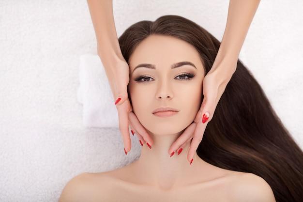 Spa. mooie jonge vrouw krijgt een gezichtsbehandeling bij schoonheidssalon.