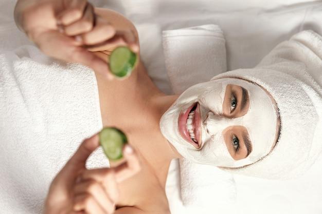 Spa. mooie vrouw met een kleimasker op haar gezicht en komkommers in handen. masker voor gezichtspeeling. huidverzorging.