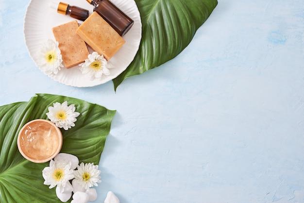 Spa-omgeving met cosmetische crème, gel, badzout en varenbladeren op blauwe achtergrond