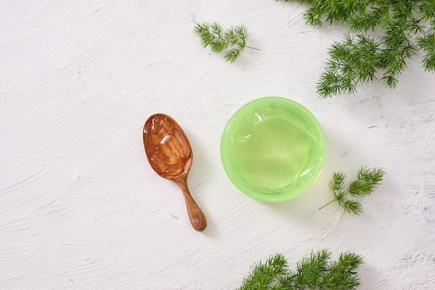 Spa-omgeving met cosmetische crème, gel, badzout en varenbladeren op witte houten tafelachtergrond
