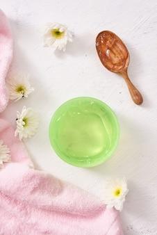 Spa-omgeving met cosmetische gel, bladeren op witte tafelachtergrond