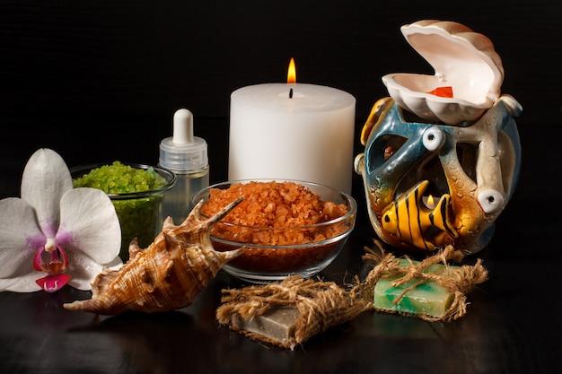 Spa-producten met orchideebloem, handgemaakte zeep, kommen met zeezout, fles met aromatische olie, kaarsen en schelp op zwarte achtergrond