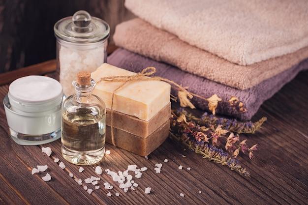 Spa-producten voor gezichts- en lichaamsverzorging. natuurlijk zeezout, zelfgemaakte zeep, massageolie en kleurrijke handdoeken. spa en lichaamsverzorging concept.