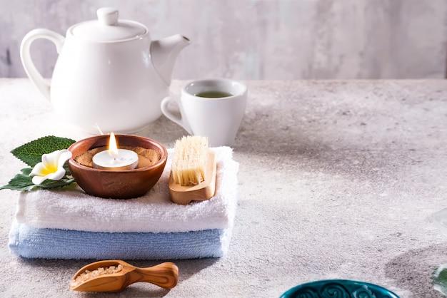 Spa resort therapie samenstelling. brandende kaarsen, handdoek, theestel en bloem op een steen, copyspace