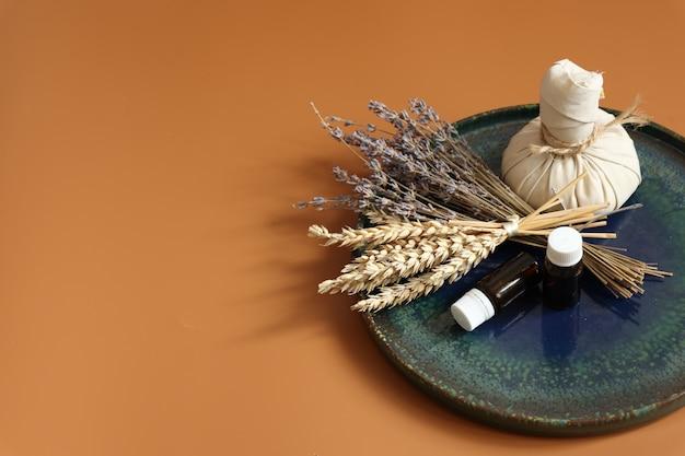 Spa-samenstelling met kruidenzak natuurlijke oliën in potten en gedroogde bloemen