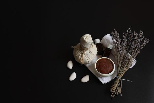 Spa-samenstelling met natuurlijke scrub, kruidenmassagezak, oliën en lavendel op een zwarte achtergrond, kopieerruimte.
