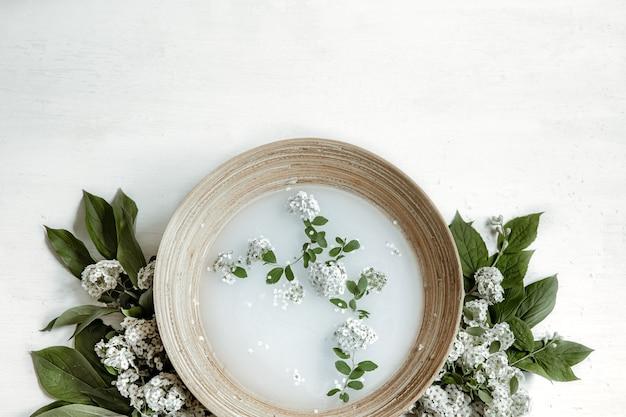 Spa-samenstelling met water voor schoonheidsbehandelingen en verse bloemen plat gelegd.