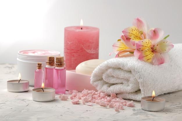 Spa-samenstelling met zeezout, aroma-oliën, handdoeken en zeep en bodyscrubs. spa-concept. op een lichte achtergrond.