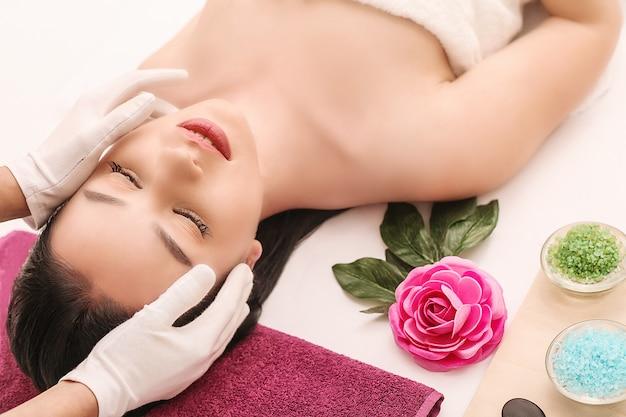 Spa, schoonheid, mensen en lichaamsverzorging, mooie vrouw die gezichtsbehandeling krijgt tijdens vakantielicht