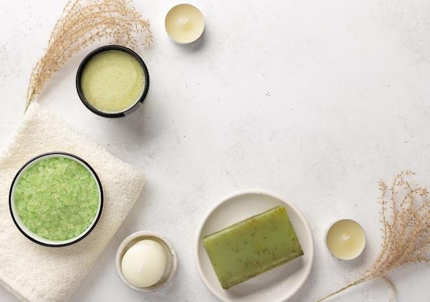 Spa set met aromatische zeezout, scrub, kruiden zeep en badhanddoeken op een witte stenen achtergrond met kaarsen, kopie ruimte