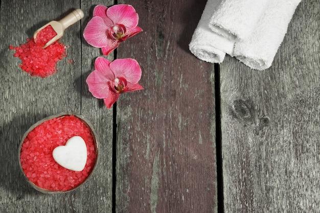 Spa set met badzout, orchidee bloemen en handdoeken op een houten achtergrond