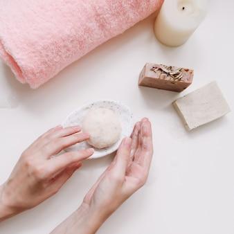 Spa-set met stuk handgemaakte zeepkaars en handdoek op wit oppervlak bovenaanzicht