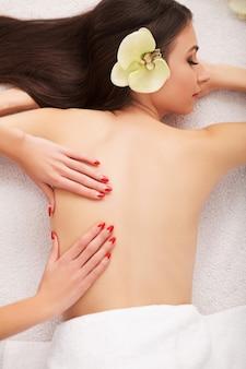 Spa steenmassage. mooie vrouw krijgt spa hete stenen massage in spa salon. schoonheidsbehandelingen outdoor. natuur