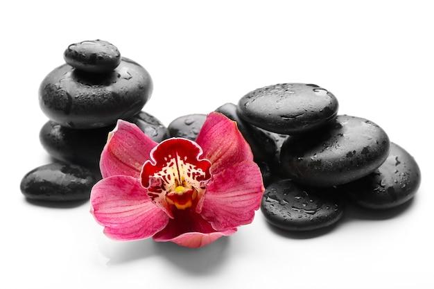 Spa stenen en rode orchidee geïsoleerd op white