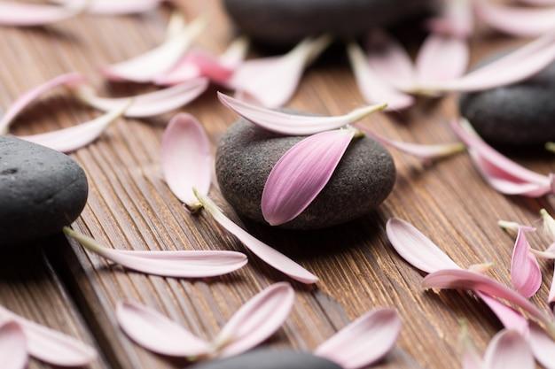 Spa stenen met bloemblaadjes. ontspannende massage.