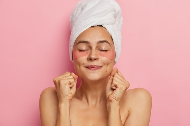 Spa-vrouw maakt masker voor haar, past hydrogelpleisters toe, balt vuisten zoals verwacht voor cosmetisch producteffect, staat shirtless met gesloten ogen