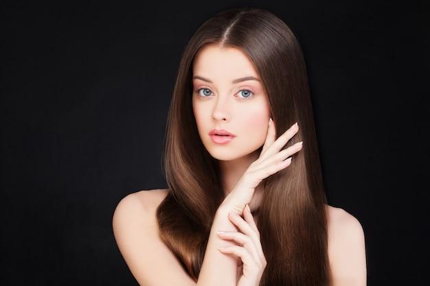 Spa vrouw met gezond haar en natuurlijke make-up op zwarte achtergrond