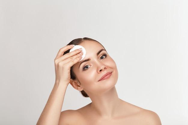 Spa vrouw. mooie vrouw die haar gezicht schoonmaakt. cosmetologie en make-up. huidsverzorging