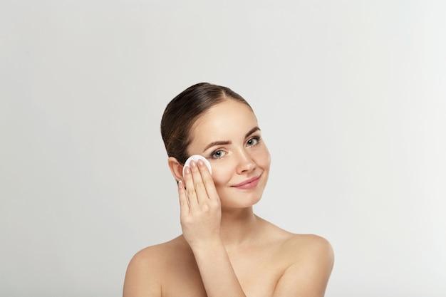 Spa vrouw. mooie vrouw die haar gezicht schoonmaakt. cosmetologie en make-up. huidverzorging