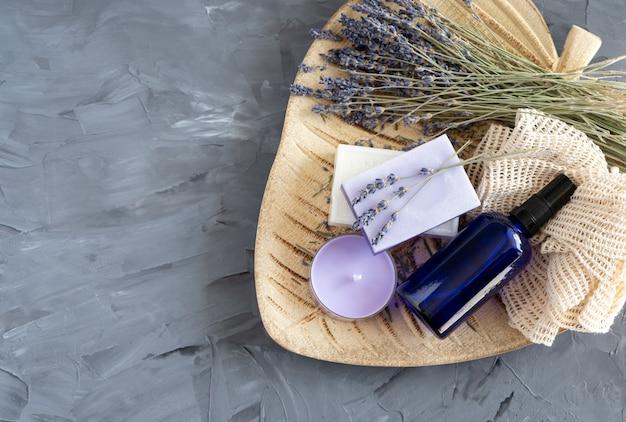 Spa zeep banner. aromatische natuurlijke zeep met lavendelbloemen, kaarsen en een fles olie op een houten bord, bovenaanzicht