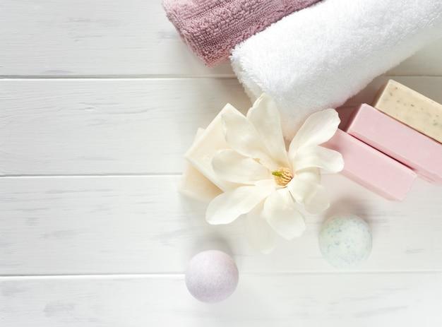 Spa zeep banner. aromatische natuurlijke zeep met magnoliabloemen en badbom op een houten witte achtergrond, bovenaanzicht