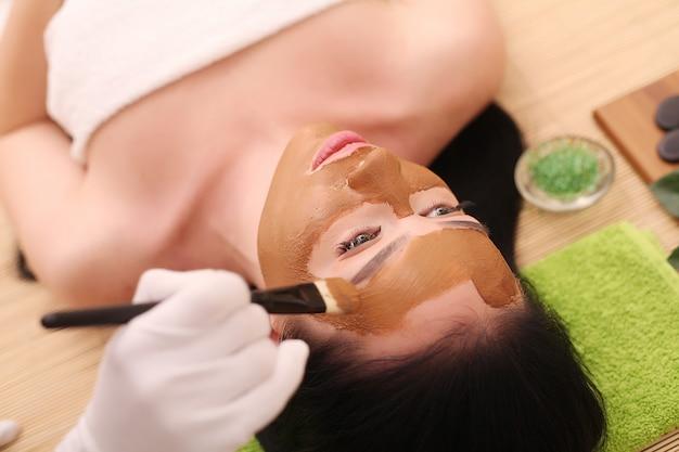 Spa. zorg gezicht. mooie jonge vrouw krijgt een gezichtsbehandeling bij schoonheidssalon