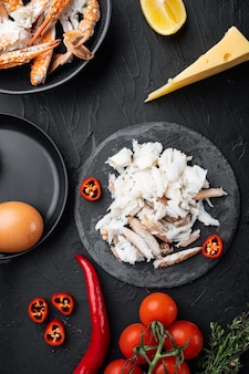 Spaans of thais omelet ingrediënt, verse rode chili, bruin en wit krabvlees, citroen, cheddar kaas, eieren set, op zwarte tafel, bovenaanzicht plat leggen
