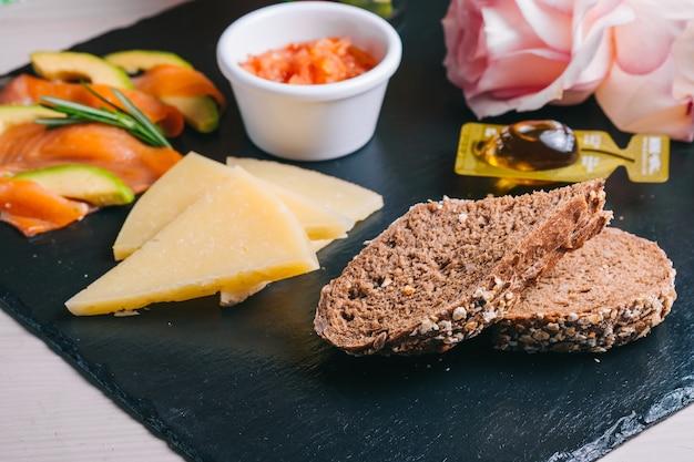 Spaans ontbijt met zalm en jamon, kaas, tomaten en sneetjes zwart brood in een zwarte plaat