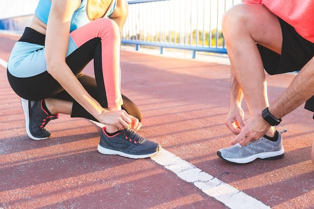 Spaans paar dat hun trainerschoenen bindt na samen in openlucht te lopen.