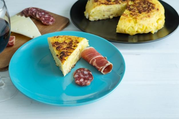 Spaanse aardappelomelet met ham en worst met kaasplankje en glas wijn op een witte achtergrond. typisch voedselconcept. kopieer ruimte.