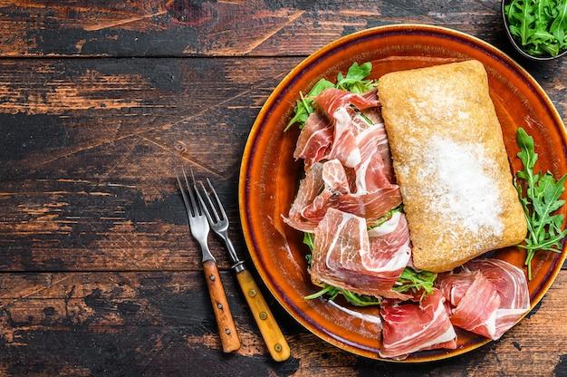 Spaanse bocadillo de jamon, sandwich met serranoham op ciabattabrood met rucola. donkere houten achtergrond. bovenaanzicht. kopieer ruimte.