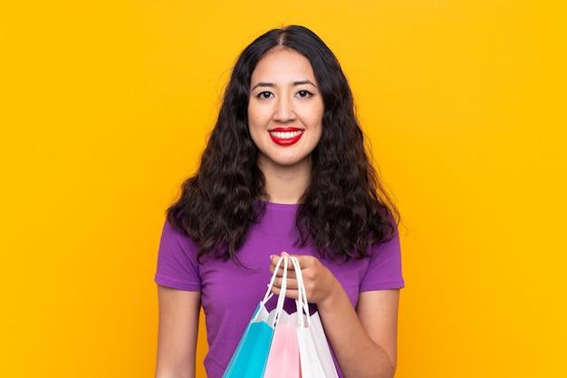 Spaanse chinese vrouw die met het winkelen zak over geïsoleerde muur veel glimlacht
