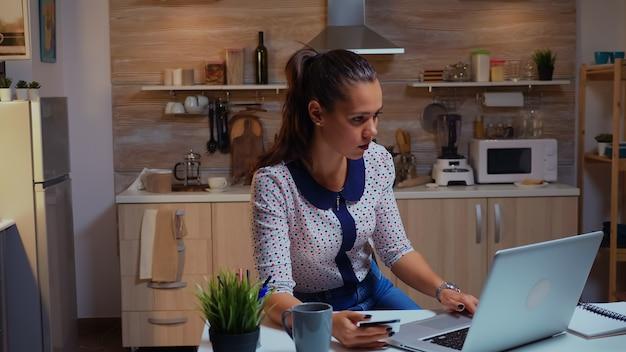 Spaanse dame die een creditcard vasthoudt terwijl ze 's avonds laat een online transactie doet met een laptop in de keuken thuis. freelancer online winkelen met elektronische betaling op digitale notebook verbonden met internet