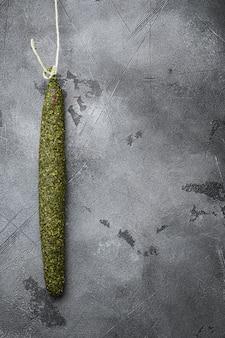 Spaanse droge salami worst fuet in kruiden op grijze achtergrond met ruimte voor tekst.
