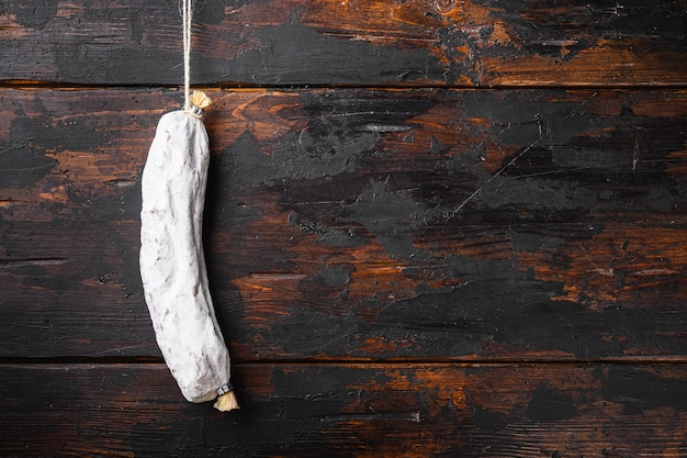 Spaanse droge salchichon worst op oude houten tafel, bovenaanzicht met ruimte voor tekst.