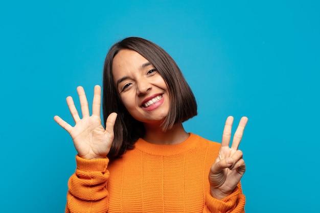 Spaanse en vrouw die vriendelijk glimlacht kijkt, nummer zeven of zevende met vooruit hand toont, aftellend