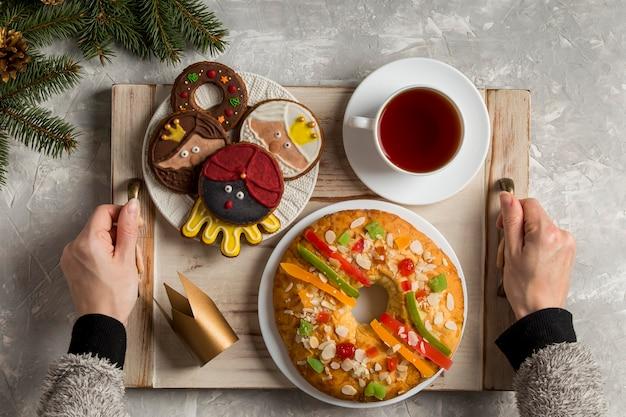 Spaanse epiphany cake roscon de reyes en persoon die het dienblad vasthoudt