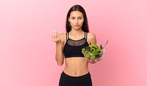 Spaanse fitnessvrouw die capice of geldgebaar maakt, zegt dat je moet betalen en een salade vasthoudt