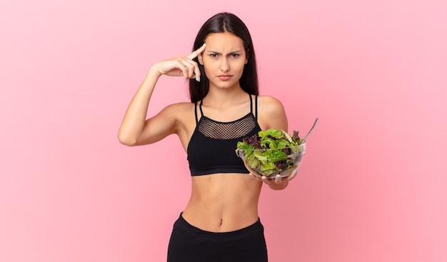 Spaanse fitnessvrouw die zich verward en verbaasd voelt, laat zien dat je gek bent en een salade vasthoudt