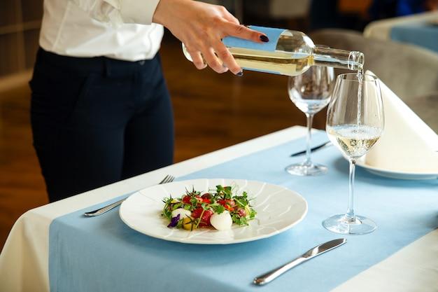 Spaanse gepelde tomatensalade met de hand van de ober die witte wijn giet