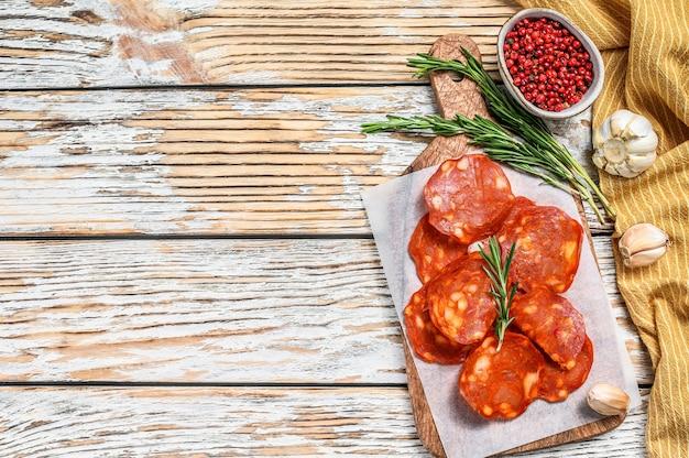 Spaanse gesneden chorizoworst op een scherpe raad. gezouten vlees. witte achtergrond. bovenaanzicht. kopieer ruimte.