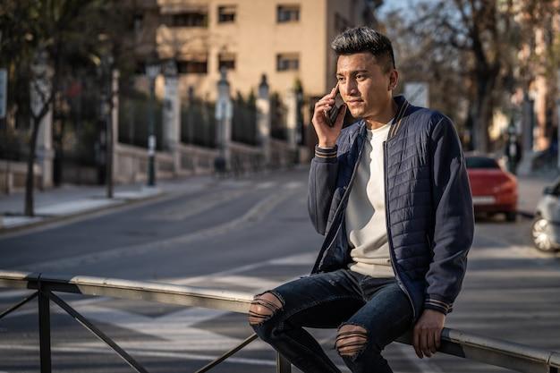 Spaanse jonge man praten met smartphone, gekleed in jeans en casual jas