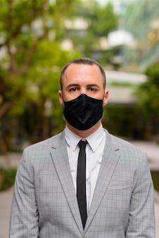 Spaanse kale zakenman die masker draagt voor bescherming tegen uitbraak van het coronavirus in de stad met de natuur